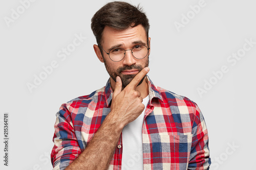 7451d2225f7 Indoor shot of thoughtful bearded young European man keeps hand under chin