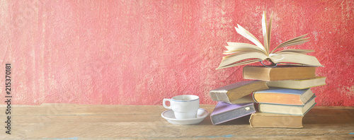 Fotografía Open Book on a pile of old books and a cup of coffee, panorama, good copy space