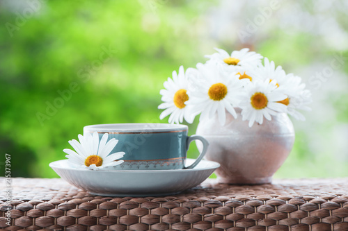 Staande foto Thee Beautiful summer composition of a cup of tea and daisy flowers on a natural green background, a concept of good morning, summer mood, happiness