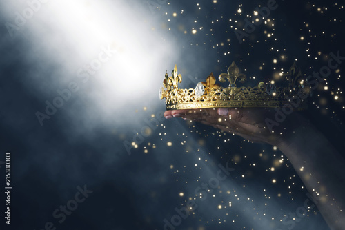 Obraz na plátně mysteriousand magical image of woman's hand holding a gold crown over gothic black background