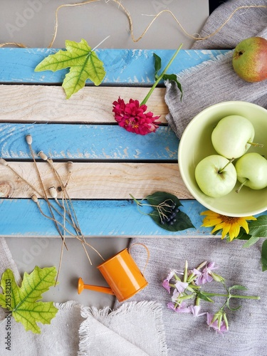 Foto  Seasonal decorative composition of flowers, leaves and fruits on a wooden light