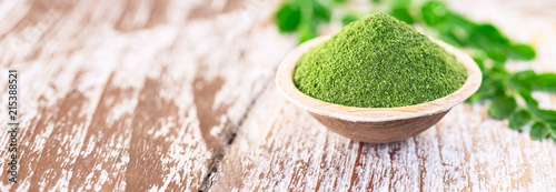 Fotografie, Obraz  Moringa powder in coconut bowl with original fresh Moringa leaves on wooden back