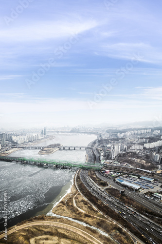 Seoul cityscape, skyline, high rise office buildings in Seoul city, winter daylight Crack on an ice surface of frozen Han river top view in winter, Seoul, Republic of Korea, in fog winter