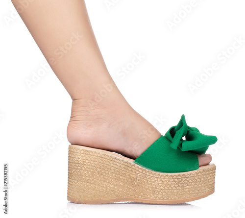 Beautiful female leg in green wedge sandals isolated on white background Fototapeta