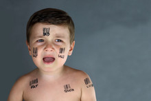 Sad Child Who Suffer Bullying With Bar Code And Insults In His Face In A Grey Background