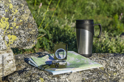 Fotografie, Obraz  a breather in the way - a map, a compass and a thermo cup on a stone on a natura
