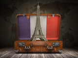 Fototapeta Wieża Eiffla - Trip to Paris. Travel or tourism to France concept. Eiffel tower andvintage suitcase with flag of France on the map of world background