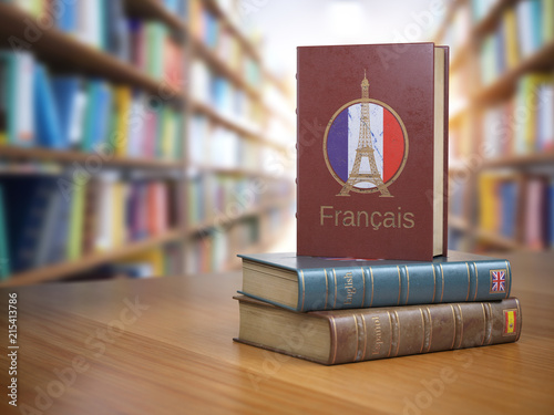 Obraz Learn French concept. French dictionary book or textbok with flag of France and Eiffel tower on the cover in the library. - fototapety do salonu