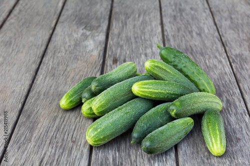 a lot of fresh green cucumbers on a board rustic table