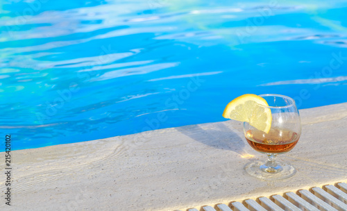 Blue pool water, a glass of flavored cognac with a slice of lemon at the water's edge