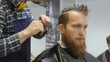 Hairdresser for men. Barbershop. Hair care. Hairdresser with a haircut works for a hairstyle for a bearded guy. The concept of a hipster lifestyle. The hairdresser cuts the hair on the back of the