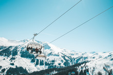 Ski Lefts And Cable Cars In The Alps Winter Resort. People Going Up For Skiing And Snowboarding. Austrian Alps