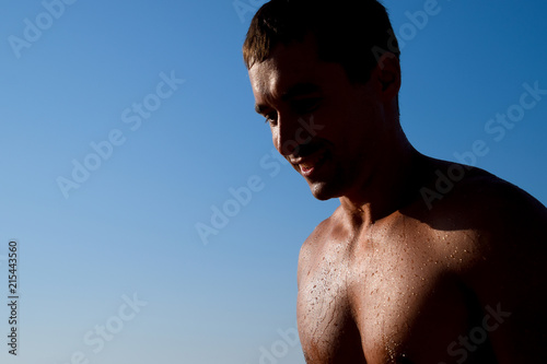 Foto op Plexiglas Akt Silhouette of a man against a blue sky and sun. A man in drops of sea water
