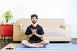 Beautiful caucasian bearded man in black clothes on blue yogamat doing lotus mudra