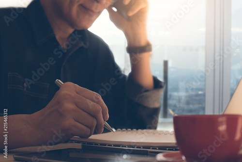 Poster  Businessman writing on notepad using smartphone