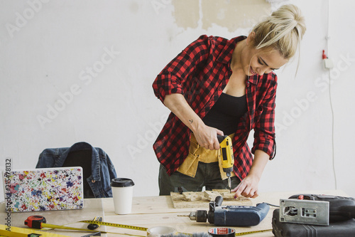 Beautiful smiling young blond woman in casual clothes drilling small piece of wood on carpenter workbench with tools, instruments and laptop on background of white plastered wall