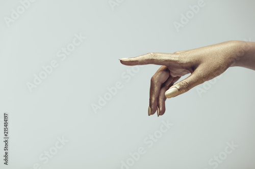 Fotografie, Tablou Golden painted hand pointing at copy space