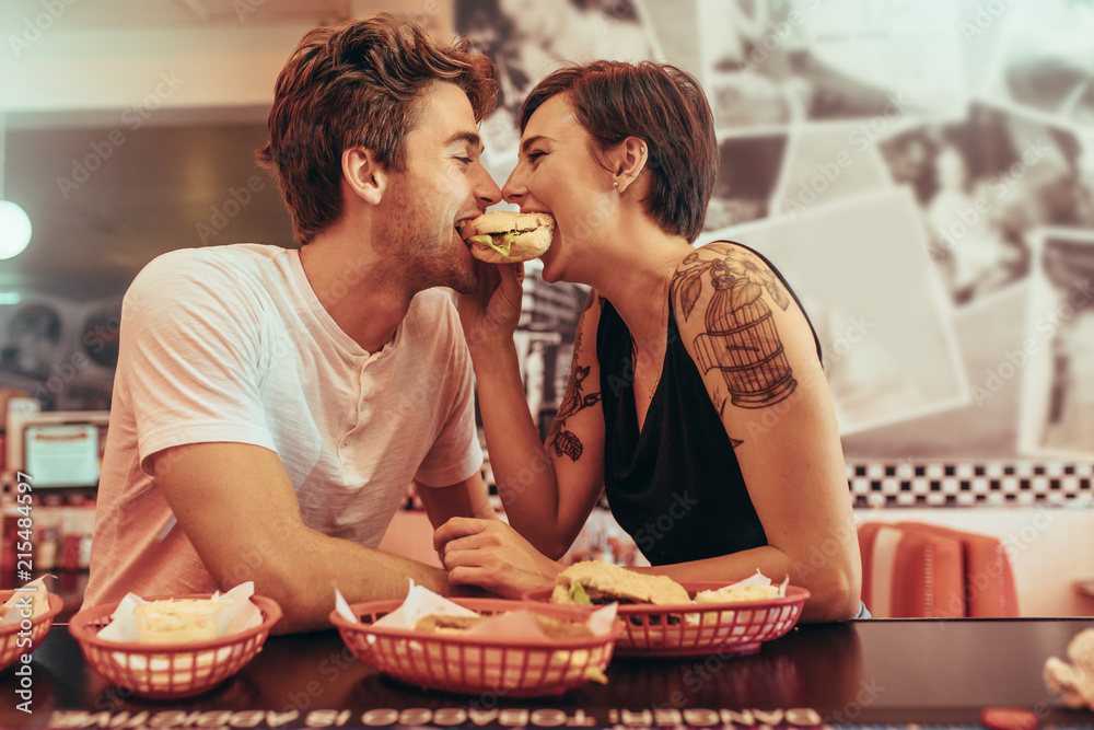Fototapeta Coupe in romantic mood sharing a burger at a restaurant
