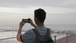 portrait of young asian man taking photo of cloudy seaside using phone