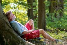 Älterer Mann Liegt Am Baum In Der Sonne