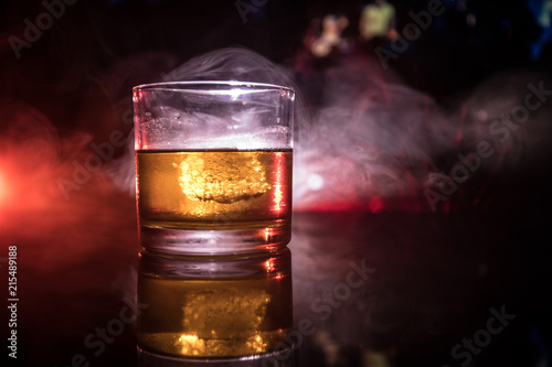 Foto op Plexiglas Alcohol selective focus pure whisky with ice cube inside whisky glass on dark foggy background alcohol drink concept.