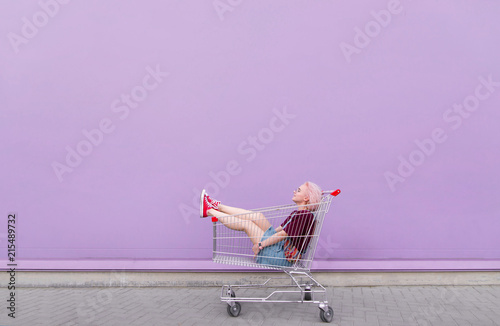Photo  Young model poses with a cart on the background of a purple wall