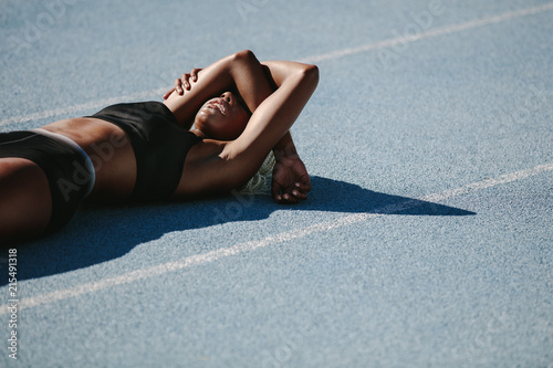 Cuadros en Lienzo Female athlete relaxing on running track after workout