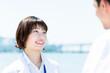 向かい合って話す女性(白衣の医者・医療従事者のイメージ)