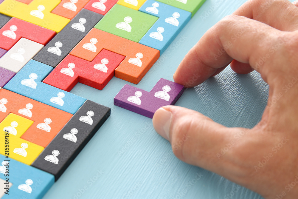 Fototapeta image of tangram puzzle blocks with people icons over wooden table ,human resources and management concept.
