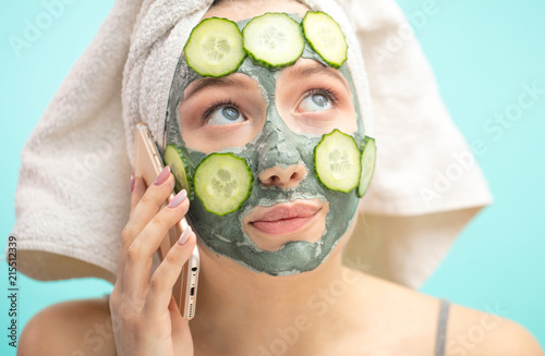 Valokuvatapetti Caucasian woman with towel on head and face mask enriching with cucumbers preparing for a date, arranging dating with her boyfriend via smartphone