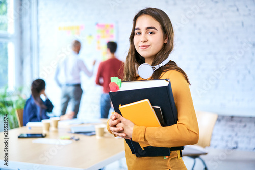 Female student standing in classroom holding books Wallpaper Mural