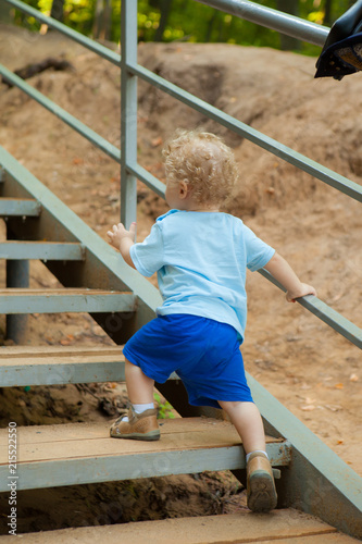 a small curly-headed boy climbs up the stairs. Ladder in the park Fototapeta