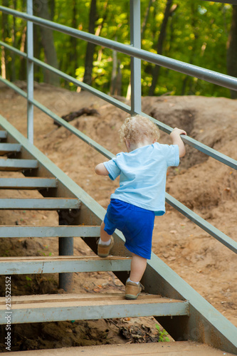 a small curly-headed boy climbs up the stairs. Ladder in the park Slika na platnu
