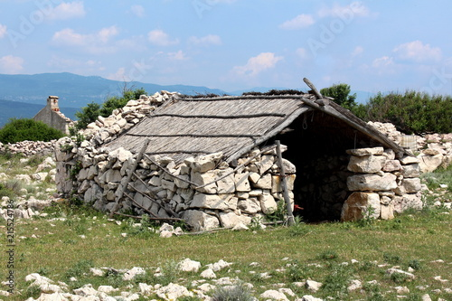 Traditional Mediterranean (Istrian) storage stone building with wood and dried hay roof surrounded with small grass and stones on warm cloudy day