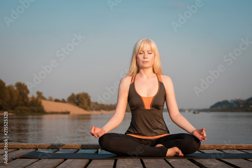 A Woman Practicing Yoga Healthy Lifestyle Yoga On The River Pier Healthy Lifestyle A Woman With Blond Hair Meditates On The Background Of The River And The Sky Buy This Stock