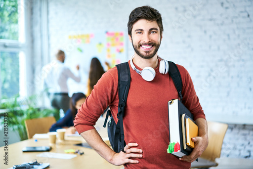 Portrait of male student standing with books in classroom and looking at camera Fototapeta