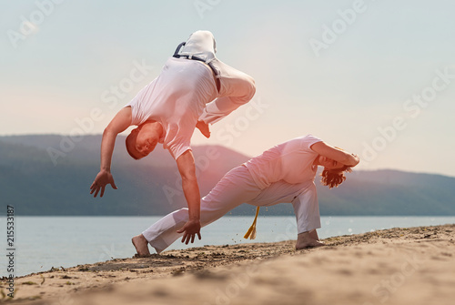 Fotografie, Tablou  Men train capoeira on the beach - concept about people, lifestyle and sport