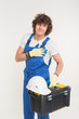 Construction, building and workers concept - Curly haired builder lifting up toolbox and white helmet in studio.