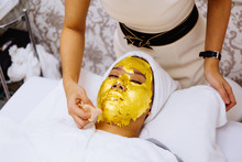 Beauty Clinic Staff Helping Young Woman Getting 24 Karat Gold Facial Treatment At The Beauty Clinic. The Treatment Of Using Real Gold For Youthful Skin.