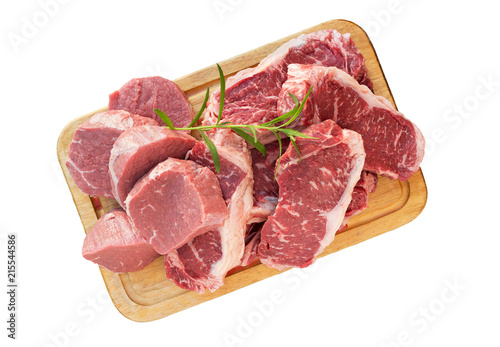 Staande foto Vlees Fresh raw beef meat steak slices on wooden cut board isolated on white.