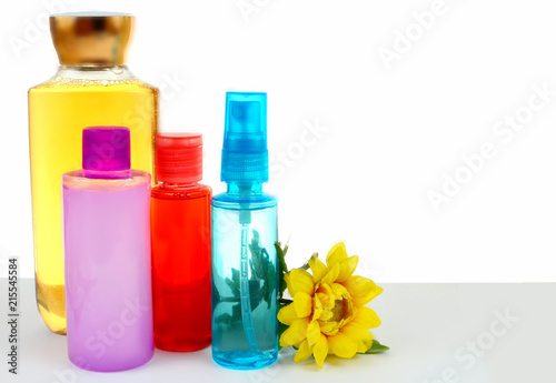 Fotografie, Obraz  Various hair and body beauty products in bright colors with a cheerful yellow chrysanthemum on white background