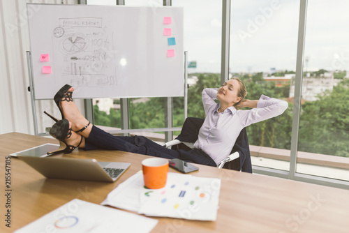 Businesswoman Relaxing With Feet Up At