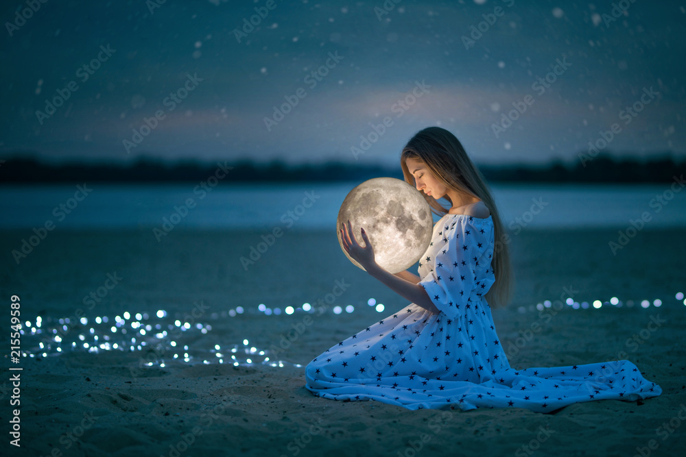 Fototapeta Beautiful attractive girl on a night beach with sand and stars hugs the moon, Artistic Photography