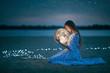 Leinwandbild Motiv Beautiful attractive girl on a night beach with sand and stars hugs the moon, Artistic Photography