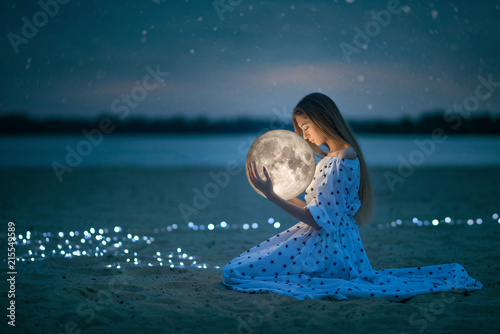 Fotografía  Beautiful attractive girl on a night beach with sand and stars hugs the moon, Ar
