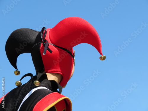Fotografía Person in a jester costume isolated on clear blue sky, carnival concept