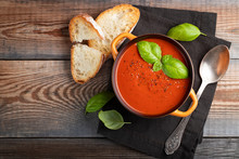 Homemade Tomato Soup With Basil, Toast And Olive Oil On A Wooden Table. Prepared A Vegetarian Dish On A Dark Background. Top View With Copy Space