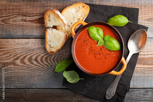 Valokuvatapetti Homemade tomato soup with Basil, toast and olive oil on a wooden table