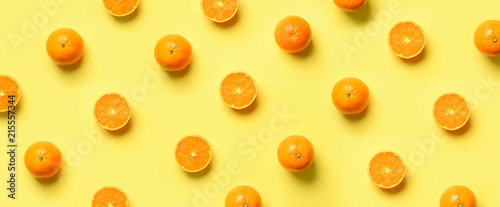 Fruit pattern of fresh orange slices on yellow background. Top view. Copy Space. Pop art design, creative summer concept. Half of citrus in minimal flat lay style. Banner. - 215557344