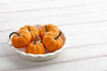 Mini Orange Pumpkins In A White Dish On Wooden Background, Holiday Decoration